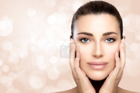 Photo pour Beauty model woman with a smooth unblemished complexion, perfect skin with no makeup makeup and hands to cheeks looking at camera with a serene expression in a skincare and spa concept. Closeup portrait over bokeh background with copy space for text - image libre de droit
