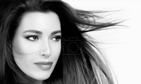 Photo for Beautiful young woman with healthy straight hair blowing to the side in a breeze. Black and white beauty portrait in a close up cropped view. - Royalty Free Image