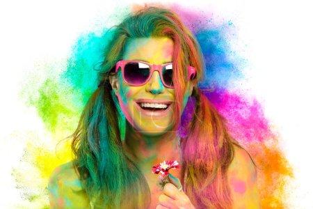 Photo pour Belle femme sensuelle couverte de poudre colorée arc-en-ciel célébrant Holi Festival portant des lunettes de soleil colorées et rouge à lèvres nu souriant à la caméra dans un concept de printemps de beauté. Magnifique jeune femme s'amuser avec de la poudre colorée - image libre de droit