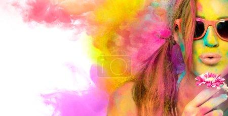 Photo pour Belle jeune femme portant des lunettes de soleil élégantes soufflant sur une fleur célébrant le festival Holi couvert de poudre de couleur vive avec des nuages de couleur gaufrer sur l'espace de copie blanche sur le côté - image libre de droit