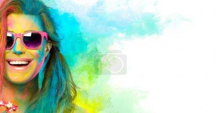 Photo pour Belle jeune femme joyeuse célébrant Holi festival des couleurs, couvert de poudre de couleur arc-en-ciel avec des lunettes de soleil roses souriant à la caméra. Superbe fête fille s'amuser avec de la poudre colorée - image libre de droit