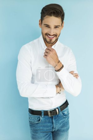 Photo for Well dressed man standing and smiling at camera on blue background - Royalty Free Image