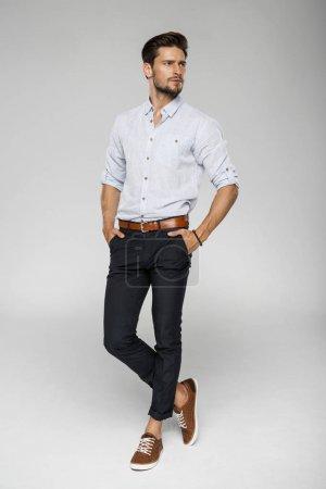 Photo pour Bel homme posant en studio, sur fond gris - image libre de droit