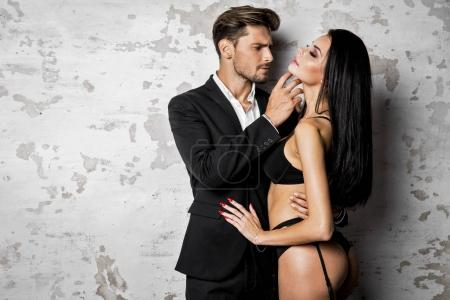 Handsome man in black suit touching sexy woman in lingerie