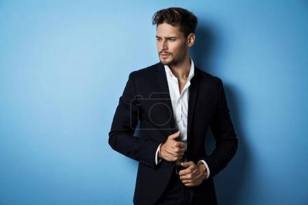 Photo pour Bel homme porter costume noir posant sur fond bleu - image libre de droit