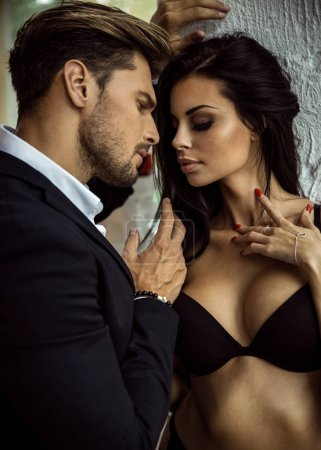 Portrait of sexy man in black suit touching sexy woman in linger
