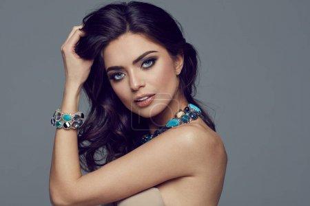 Photo pour Magnifique modèle féminin avec bijoux posant contre le gris - image libre de droit