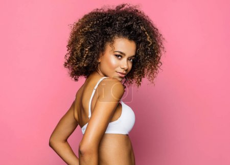 Photo for Beautiful african american young woman in white bra with an afro hairstyle posing on pink background - Royalty Free Image
