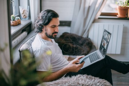 Photo for Workplace at home. A man works on a laptop at home, sits on a sofa in the living room during the day, talks on the phone. Work from home. - Royalty Free Image