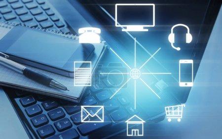 Photo pour Smartphone et bloc-notes couchés sur ordinateur portable et différentes icônes en cercle. Canal Omni - image libre de droit