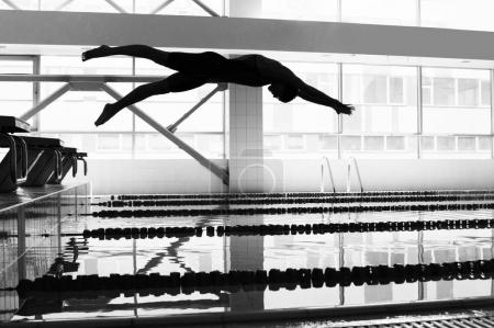 Photo for Prosfessional swimmer jumping in to the pool - Royalty Free Image