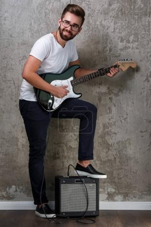 Photo for Stylish bearded guy with a guitar - Royalty Free Image
