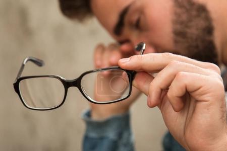 Photo pour Homme avec des yeux fatigués après un long travail tenant ses lunettes - image libre de droit