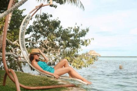 Foto de Hermosa mujer de relax en hamacas al lado del lago - Imagen libre de derechos
