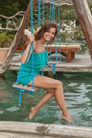 Photo pour Une femme belle et heureuse sur la balançoire qui au-dessus de l'eau - image libre de droit