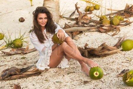 Photo pour Belle femme et beaucoup de noix de coco sur le sol - image libre de droit