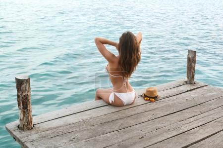 Beautiful in the bikini on the wooden pier