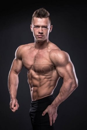 Photo for Young bodybuilder showing his muscles in studio - Royalty Free Image