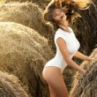Sexy young woman in white bodysuit among the hayst...