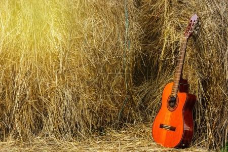 Acoustic guitar near haystacks