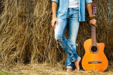 Male legs and acoustic guitar