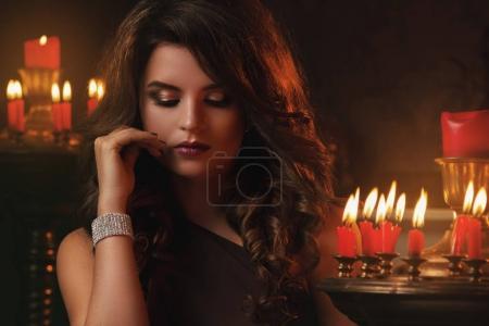 Photo pour Belle femme dans la chambre noire avec des bougies - image libre de droit