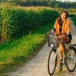 Young happy woman cycling on country road near cor...