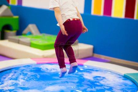 Photo pour Enfant d'âge préscolaire avec des queues de cheval dans un T-shirt blanc sauté sur un trampoline gonflable avec rétro-éclairage sur l'aire de jeux . - image libre de droit