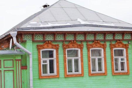 Photo pour Vieille maison en bois de couleur verte avec de beaux platanes bruns sur les fenêtres. - image libre de droit