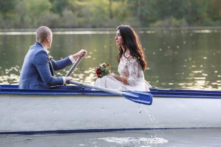 Photo pour Les mariés se tiennent près du lac, après la cérémonie de mariage. Les jeunes mariés sourient, ils sont heureux. Photo en silhouette dans une teinte chaude. Rétroéclairage . - image libre de droit
