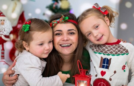 Photo for Portrait of mother hugging her daughters on Christmas Eve - Royalty Free Image