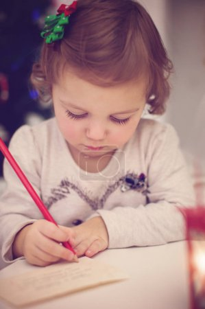 Photo for Closeup Christmas portrait of cute little baby writes letter to Sant - Royalty Free Image