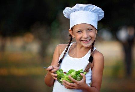 Photo pour Gros plan portrait de mignonne petite fille manger de la salade - image libre de droit
