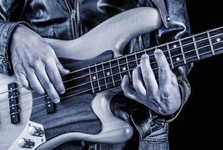 Photo for Hands of rock bassist playing electric bass guitar,blue image - Royalty Free Image
