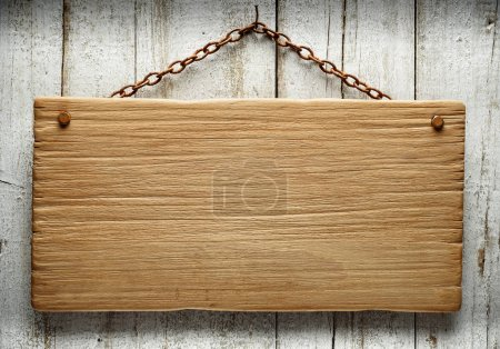 Photo for Old wooden signboard hanging on an aged wall with a rusty chain - Royalty Free Image