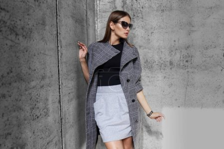 Photo pour Haute couture portrait de jeune femme élégante en manteau gris et lunettes de soleil en plein air, sur fond de mur gris - image libre de droit