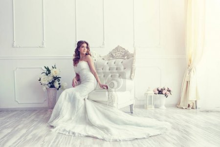 Photo for Young beautiful bride sitting in antique armchair - Royalty Free Image