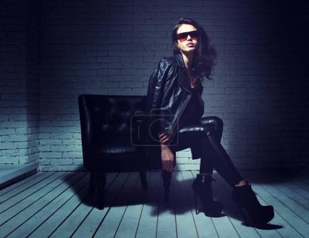 Photo pour Mannequin en lunettes de soleil, veste en cuir noir, pantalon en cuir. Assis dans le fauteuil en cuir vintage. - image libre de droit