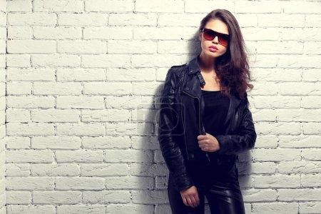 Photo pour Mannequin en lunettes de soleil, veste en cuir noir, pantalon en cuir. Posant près de mur de briques blanches. - image libre de droit