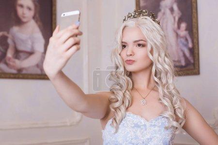 Photo pour Une belle jeune femme dans la couronne fait une auto, prend des photos d'elle-même sur un téléphone cher. Princesse, la reine dans le château. Fille d'un oligarque, fonctionnaire. - image libre de droit