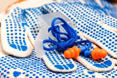 Photo pour Gants de travail léger avec boutons bleus et des bouchons d'oreille fermer vers le haut, fond de l'équipement de protection individuelle. Concept de sécurité industrielle. - image libre de droit