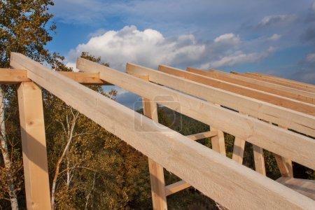 Photo pour Poutres du toit. Soirée automnale ensoleillée sur le site de construction d'une maison en bois. Maison inachevée. - image libre de droit