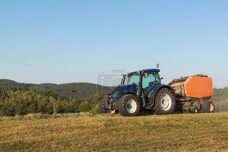 Photo pour Tracteur bleu sur le pâturage.. Travaux agricoles à la ferme en République tchèque - image libre de droit