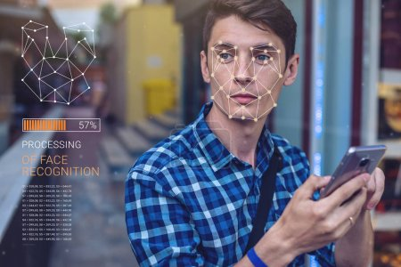 Photo pour Vérification biométrique. Jeune homme moderne avec le téléphone. Le concept d'une nouvelle technologie de reconnaissance faciale sur grille polygonale est construit par les points de sécurité et de protection des TI - image libre de droit