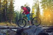 Cyclist with a backpack on a mountain bike in the forest at sunset. Concept of an active lifestyle with nature