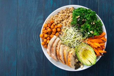 Photo for Buddha bowl with kale salad, quinoa, roasted chickpeas, grilled chicken breast, avocado, baked sweet potatoes, leek sprouted seeds, pine nuts, sesame and seeds. - Royalty Free Image