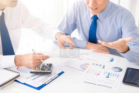 Photo pour Deux hommes d'affaires discutent de documents financiers à la table de réunion - image libre de droit