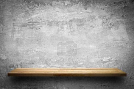 Empty wood shelf on bare concrete wall background