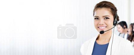 Photo pour Femme souriante portant un casque microphone comme opérateur, télévendeur, centre d'appels et personnel du service à la clientèle - arrière-plan panoramique ou bannière avec espace vide - image libre de droit