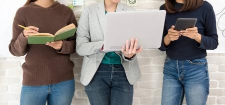 Photo pour Trois étudiantes debout et tenant un livre, un ordinateur portable et une tablette - image libre de droit